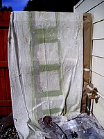 Wood fence covered with drop cloth and paper.