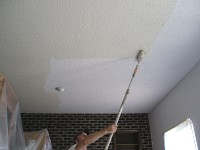 Rolling paint on an acoustical ceiling.