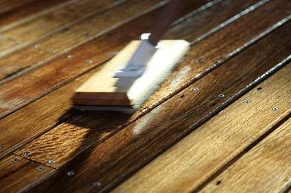 Applying wood sealer to deck floor boards using a staining-pad.