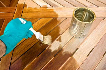 Applying Tung oil to cleaned and sanded smooth teak patio table top.
