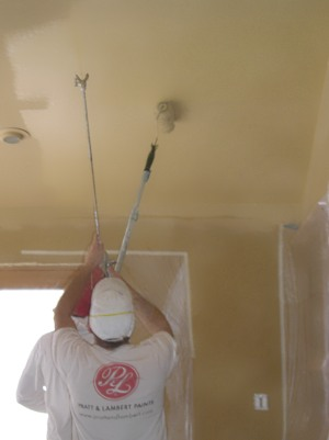 Spraying then back-rolling interior ceiling paint.