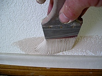 Using a brush to cut-in thw wall to the base.