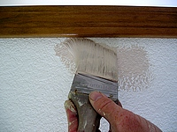 Using a brush to cut-in the wall to the trim.