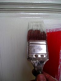 Applying paint to a door with a brush.