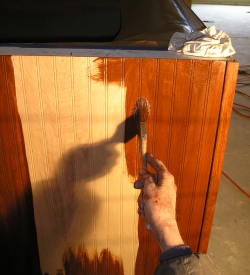 Applying wood stain to a cabinet with a brush, just before wiping off the stain with a rag.