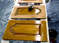 Applying stain to cabinet doors.