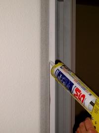 Using siliconized acrylic caulk on a door frame.