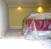 An interior room prepared for painting, fully covered including the floor and furniture.