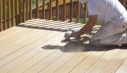 Using a large angle grinder and coarse sanding discs to remove the old stain from a wood deck.