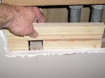 Installing a piece of 1x6 as a furring strip/backing for new drywall.