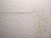 A stress crack in a textured ceiling.