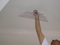 Leveling off the sprayed drywall mud to knock-down the texture.