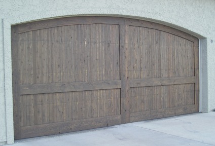 A wide cedar wood garage door stained with 2 coats of a semi-transparent exterior stain.