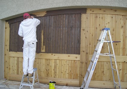 Applying the first coat of oil base exterior wood stain to a cedar wood garage door.