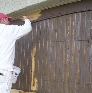 Close-up of staining a wood garage door.