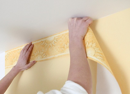 Hanging a wallpaper border along the ceiling.