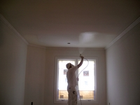 Spraying paint on interior ceiling.