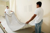 Laying down a drop cloth to protect the floor during painting.
