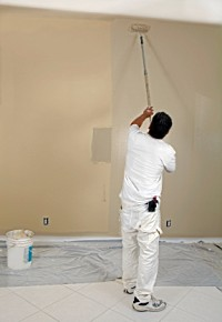 Applying paint with a roller to an interior room.
