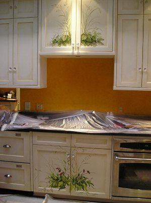 Beautifully painted and antiqued kitchen cabinets.