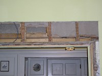 Large open hole in plaster wall. Wall framing is exposed above doorway opening.