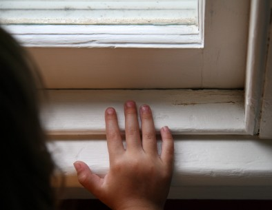 Child touching a window sill with old peeling lead paint.