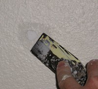 Spackling a minor dent in drywall wall.