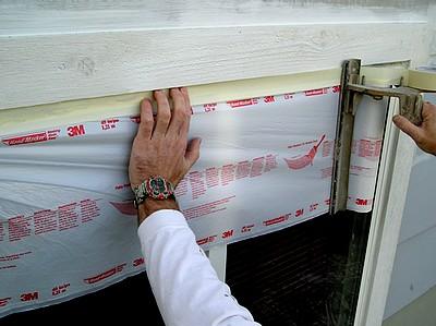 Applying plastic masking film to exterior windows.