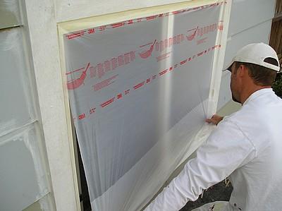 Unfolding plastic masking film on exterior window.