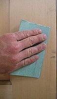 Hand sanding new interior wood door.