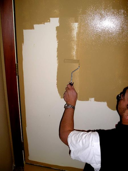 Applying paint with a roller close to a steel door.