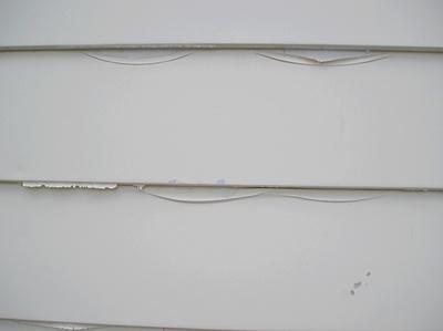 Peeling paint on steel siding.