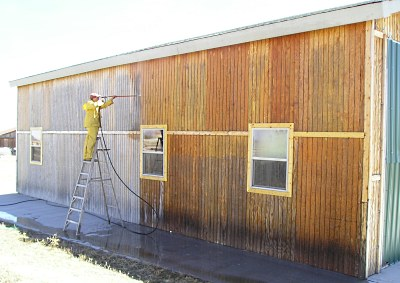 Pressure washing T1-11 siding on a aircraft hanger.