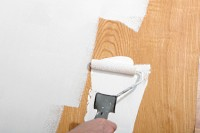 Applying primer to wood paneling.