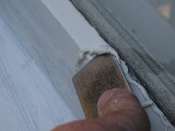 Smoothing glazing compound with a putty knife.
