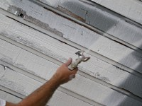 Using an airless paint sprayer to prime rough sawn lumber siding.