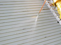 Pressure washing rough sawn lumber siding with peeling paint.
