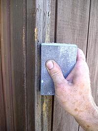 Hand sanding exterior wood door frame.