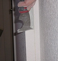 Scraping loose drywall compound from metal drywall cornerbead.