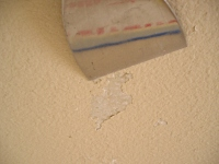 Using a stiff broad putty knife to remove loose paint on a wall.