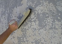 Scraping loose paint on stucco using a wire brush.