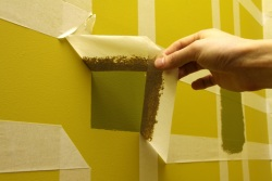 Painting squares on a wall- removing the making tape to reveal the pattern.
