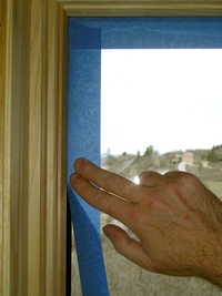 Applying blue tape to glass.