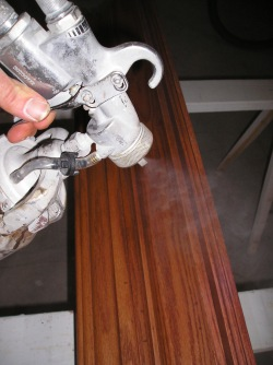 Applying a clear finish to a piece of wood trim using an HVLP sprayer.