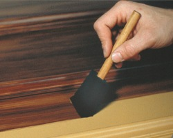 Applying glaze with a sponge brush before making a faux oak wood graining effect.