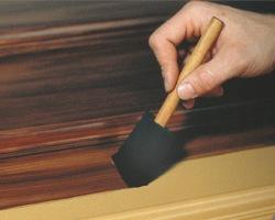 Applying glaze with a sponge brush before making a faux oak wood graining effect.