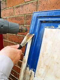Using a heat gun to strip paint from door.