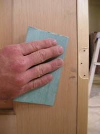 Removing a blemish on a solid wood interior door by hand sanding.