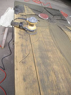 Sanding off the old finish from a solid wood front door.