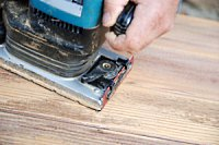 Using a sander to remove varnish from wood.